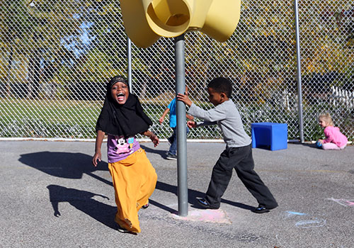 Mana and her new friend enjoy the sunshine and outdoor games at Puritas Head Start.