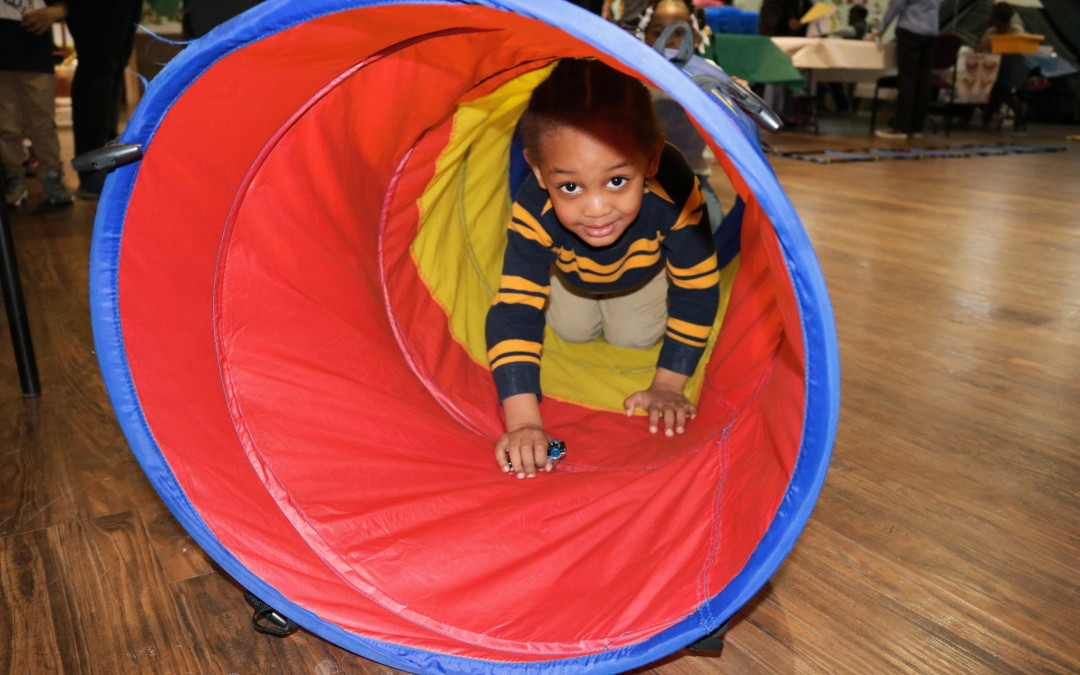 Carter, 3, crawls through a tube at the end of the Fit You! obstacle course.