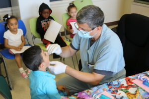 Dentist Nameer Al-Hashimi, a Clinical Instructor at Case Western Reserve School of Dental Medicine, checks 4-year-old Marvin's teeth while the other kids wait patiently.