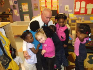 Bellaire Head Start students hug Commander McCartney after he reads them a book.